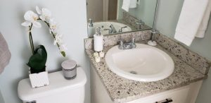A downward shot facing a bathroom area. Granite counter tops replacing porcelain.